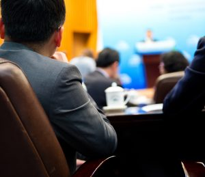 Rear view of business people listening attentively at conference.